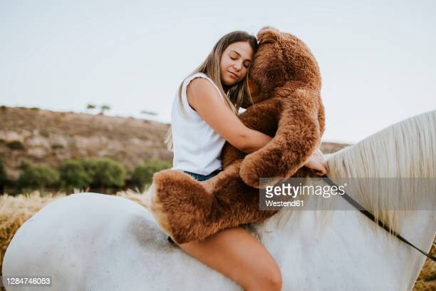 portrait of beautiful young woman embracing large teddy bear while sitting on horseback with closed eyes - teddy bear stock pictures, royalty-free photos & images