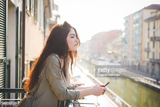 Portrait of beautiful young woman gazing from waterfront balcony