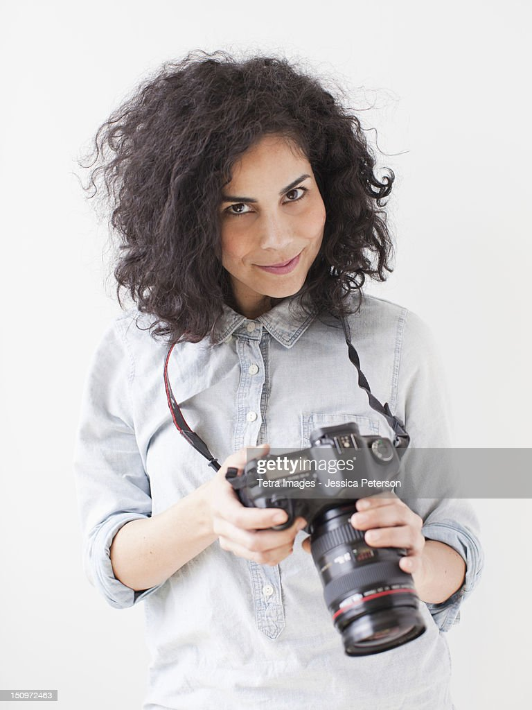 Portrait of beautiful young woman holding professional camera : Stock Photo