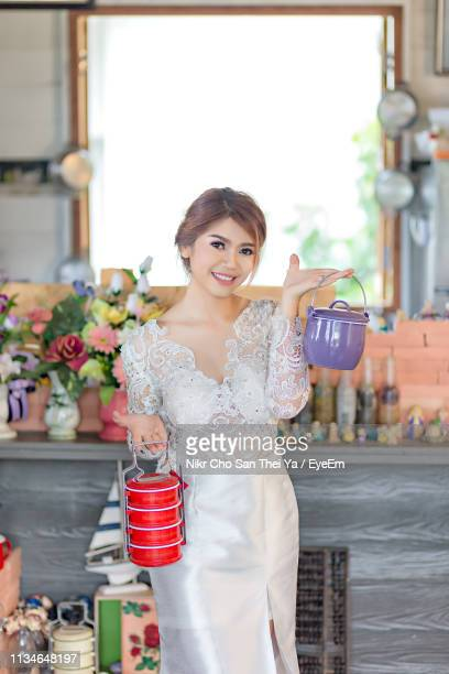 portrait of beautiful young woman holding tiffin boxes at home - tiffin box photos et images de collection