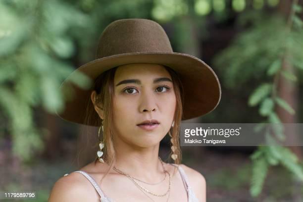 portrait of beautiful young woman in park - makiko tanigawa ストックフォトと画像