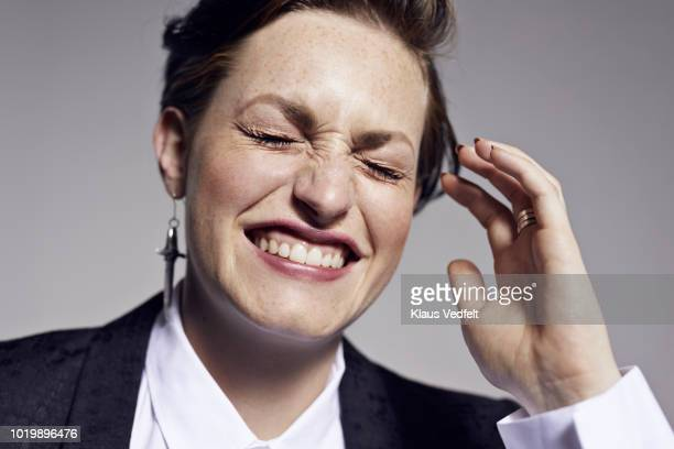 portrait of beautiful young woman laughing with closed eyes, shot on studio - non binary gender stock pictures, royalty-free photos & images
