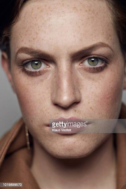 portrait of beautiful young woman looking in camera, shot on studio - junge frau allein fotos stock-fotos und bilder