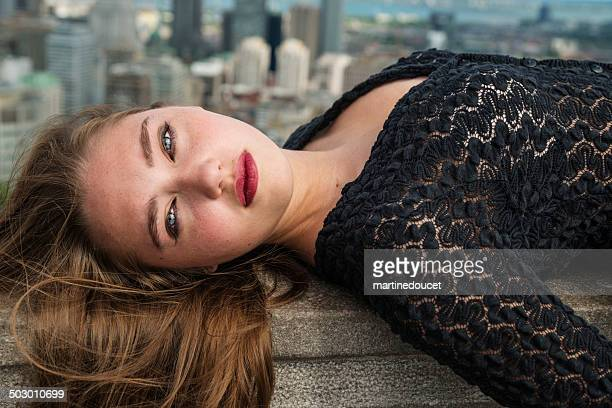 Portrait of beautiful young woman lying in front of cityscape.