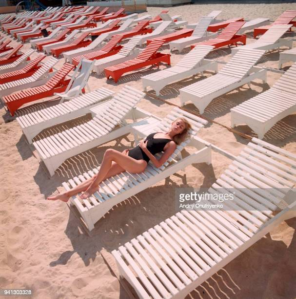 Portrait of beautiful young woman lying on a beach chaise