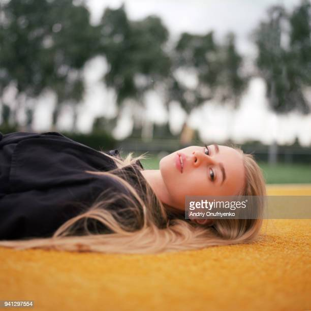 Portrait of beautiful young woman lying on tennis court