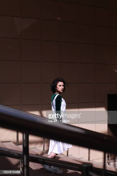 portrait of beautiful young woman moving down on steps - focus on background stock pictures, royalty-free photos & images