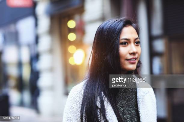 Portrait of beautiful young woman on city street