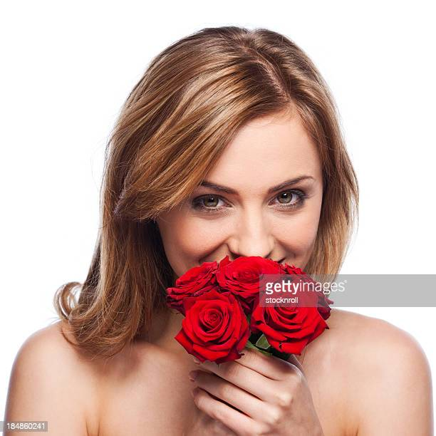 Portrait of beautiful young woman on white background smelling roses.