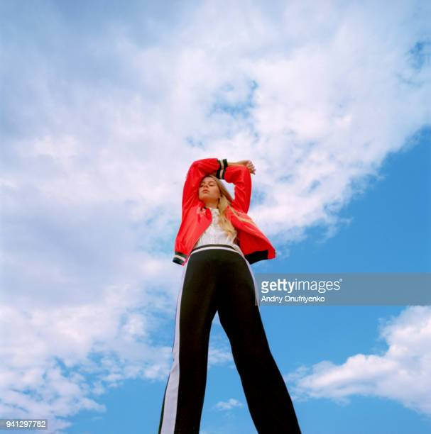 portrait of beautiful young woman over blue sky - moda fotografías e imágenes de stock