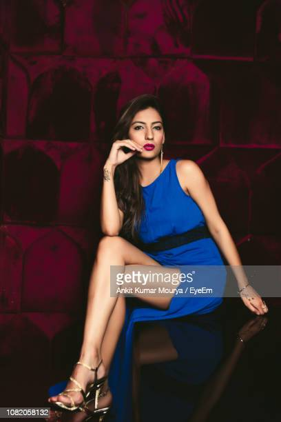 portrait of beautiful young woman posing in blue dress - blue dress stock pictures, royalty-free photos & images