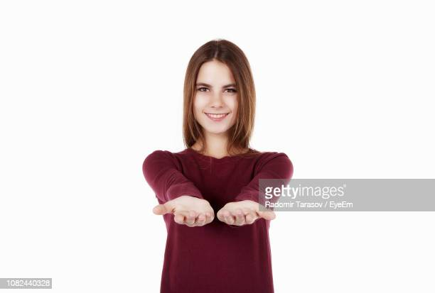 portrait of beautiful young woman presenting empty hands against white background - 手のひら ストックフォトと画像