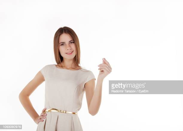 portrait of beautiful young woman showing hand pinch while standing against white background - cut out dress stock pictures, royalty-free photos & images