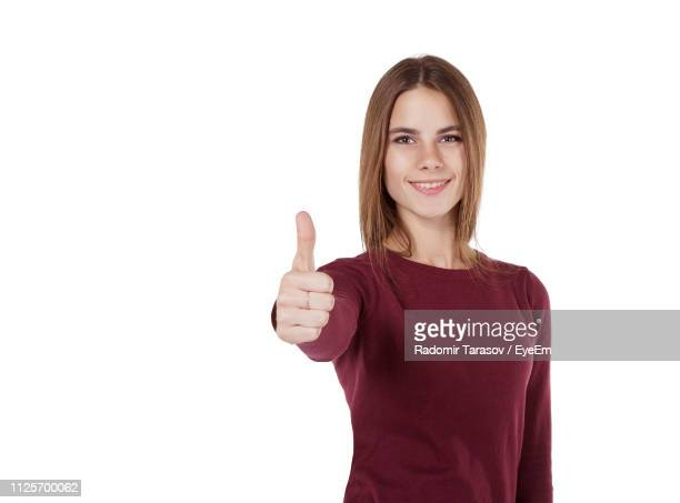 portrait of beautiful young woman showing thumb up sign against white background - langärmlig stock-fotos und bilder