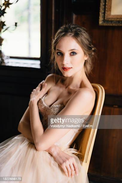 portrait of beautiful young woman sitting at home - evening gown stock pictures, royalty-free photos & images