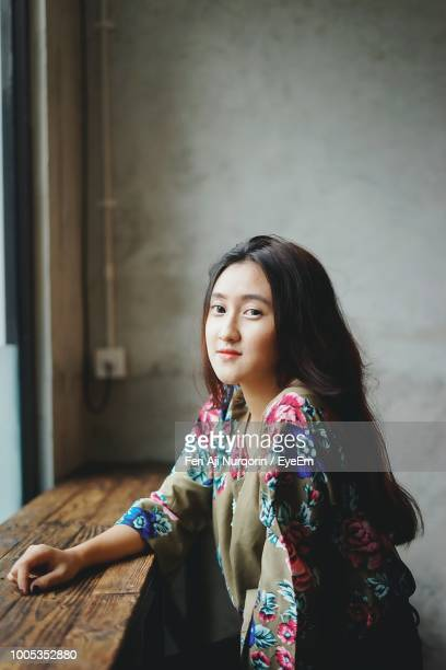 Portrait Of Beautiful Young Woman Sitting At Wooden Table