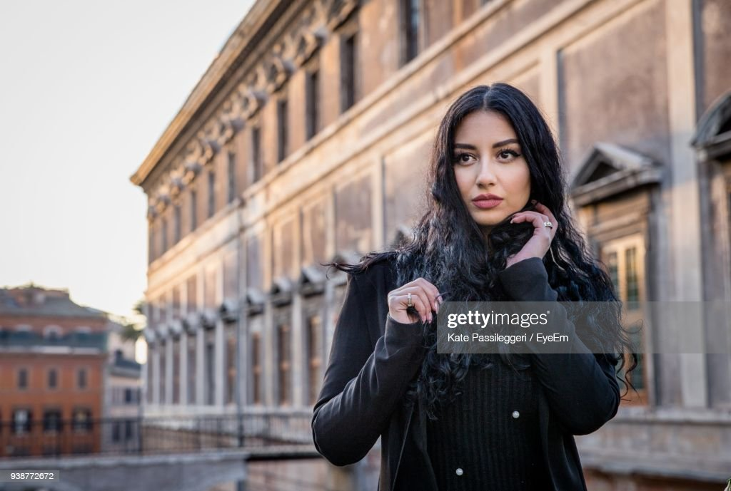 Portrait Of Beautiful Young Woman Standing Against Building : Stock Photo