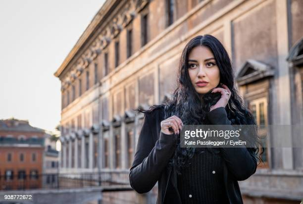 portrait of beautiful young woman standing against building - iranian woman stock photos and pictures