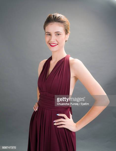 Portrait Of Beautiful Young Woman Standing Against Gray Background