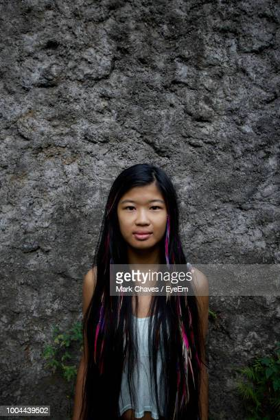 Portrait Of Beautiful Young Woman Standing Against Rock