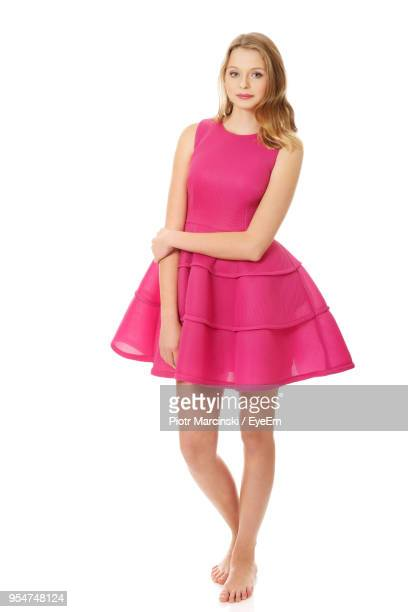 portrait of beautiful young woman standing against white background - pink dress stock photos and pictures