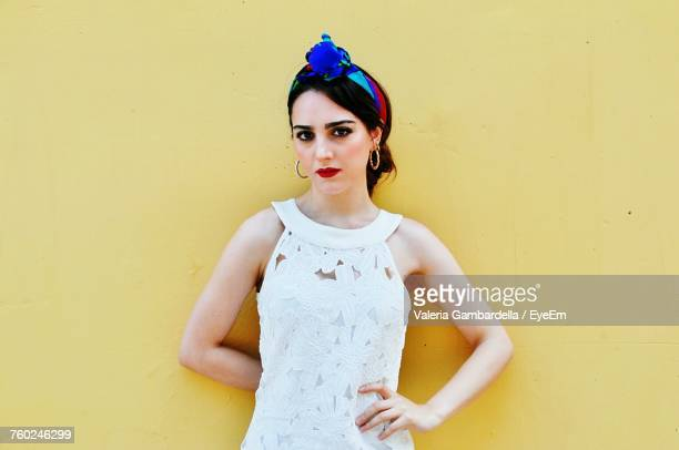 portrait of beautiful young woman standing against yellow wall - sleeveless stock pictures, royalty-free photos & images