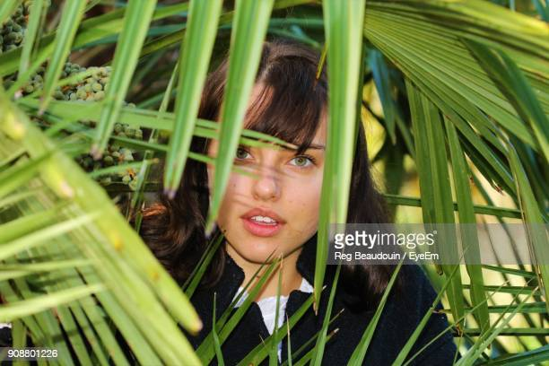 Portrait Of Beautiful Young Woman Standing Amidst Leaves