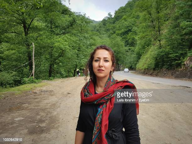 portrait of beautiful young woman standing at roadside against trees - neckwear stock pictures, royalty-free photos & images