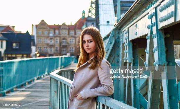 portrait of beautiful young woman standing by railing on bridge - rademann stock pictures, royalty-free photos & images