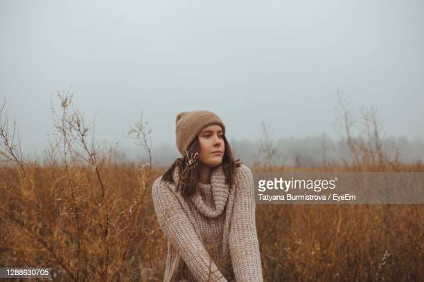 portrait of beautiful young woman standing in a fog against sky during late autumn winter - russia stock pictures, royalty-free photos & images