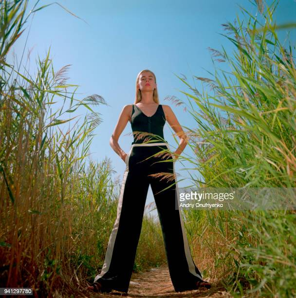 Portrait of beautiful young woman standing in a tall grass
