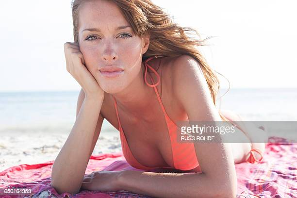 Portrait of beautiful young woman sunbathing on beach, Majorca, Spain