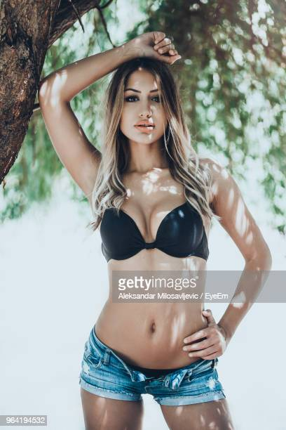 713bd865247e Portrait Of Beautiful Young Woman Wearing Bikini Top And Hot Pants By Tree  Stock Photo - Getty Images