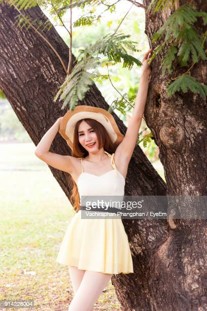 Portrait Of Beautiful Young Woman Wearing Hat While Standing By Tree Trunk