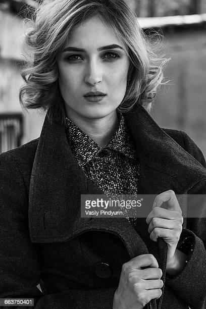 Portrait of beautiful young woman wearing long coat outdoors
