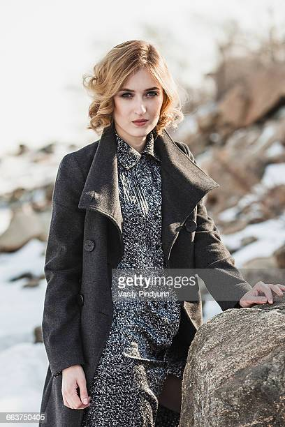 Portrait of beautiful young woman wearing long coat while standing by rock