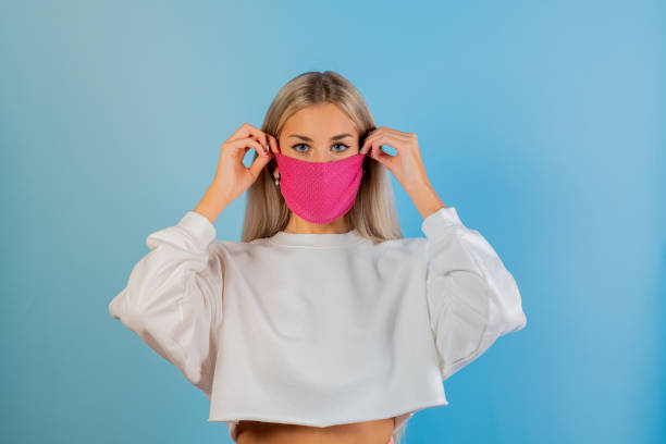 Portrait Of Beautiful Young Woman Wearing Mask Against Blue Background