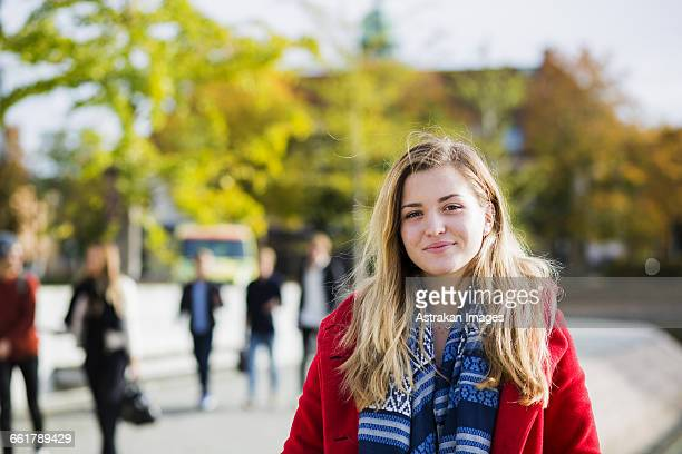 Portrait of beautiful young woman wearing red jacket outdoors