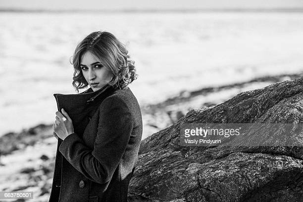 Portrait of beautiful young woman wearing winter coat while standing by rock