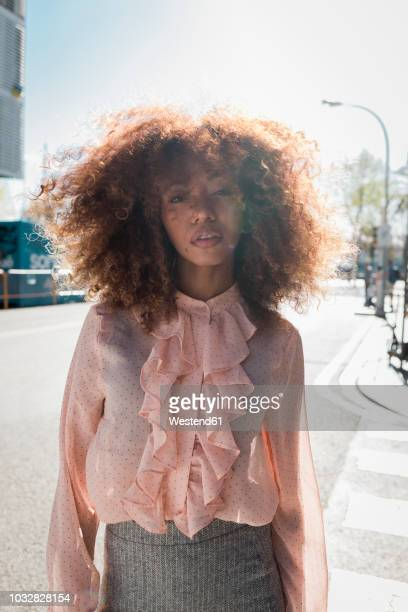 portrait of beautiful young woman with afro hairdo in the city - blouse stock pictures, royalty-free photos & images