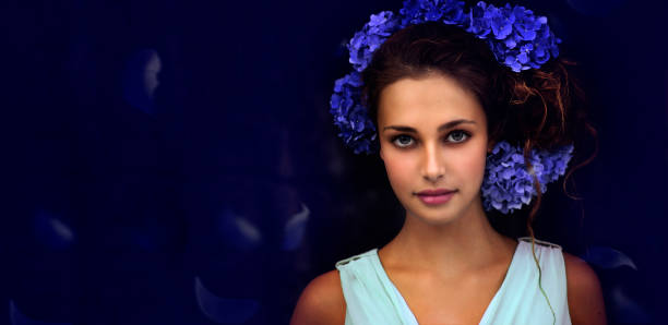 Portrait Of Beautiful Young Woman With Blue Velvet Backdrop And Flowers