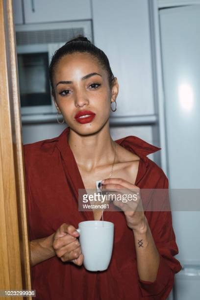 Portrait of beautiful young woman with cup of tea at home
