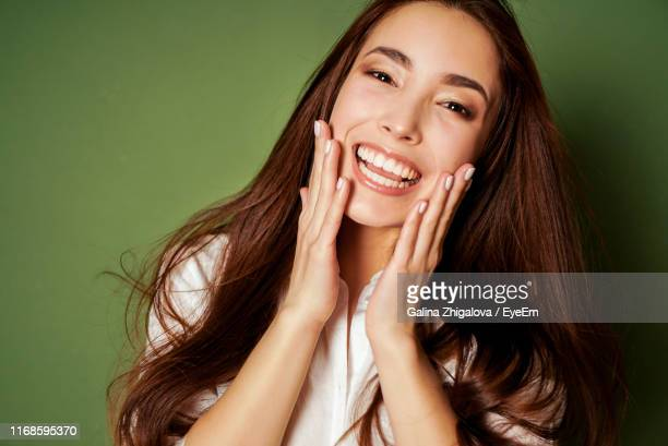portrait of beautiful young woman with hand on cheek against green background - 頬 ストックフォトと画像
