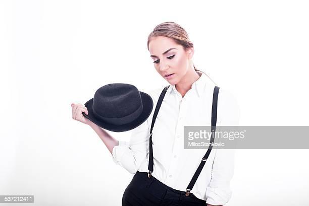 Retrato de una bella mujer joven con sombrero de hombre