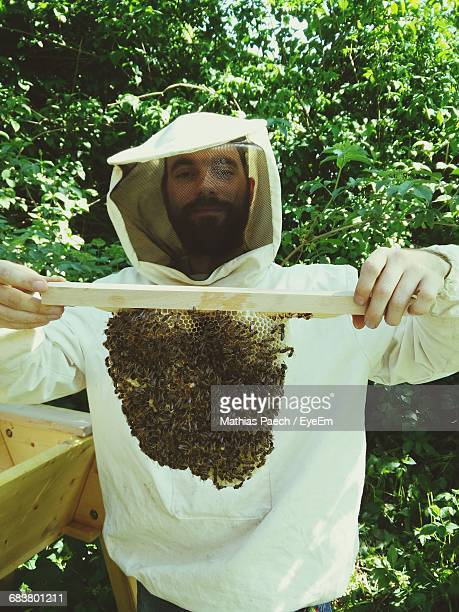 Portrait Of Beekeeper Holding Honeycomb
