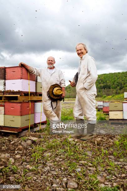 portrait of beekeepers standing by containers in farm - 養蜂 ストックフォトと画像