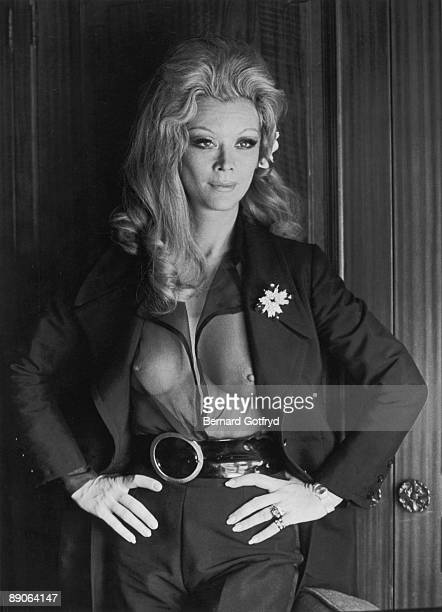 Portrait of Belgian actress Monique Van Vooren as she poses with her hands on her hips dressed in a transparent shirt under her opne jacket 1970s