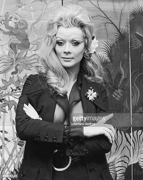 Portrait of Belgian actress Monique Van Vooren as she poses with her arms crossed over a jacket and transparent shirt 1970s