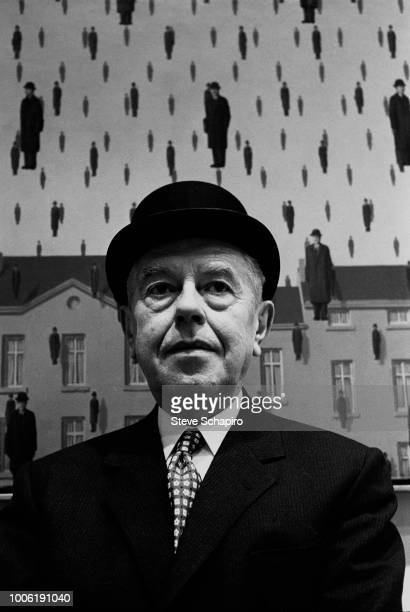 Portrait of Belgian artist Rene Magritte as he poses in front of his painting 'Golconda' during an exhibition at the Museum of Modern Art New York...