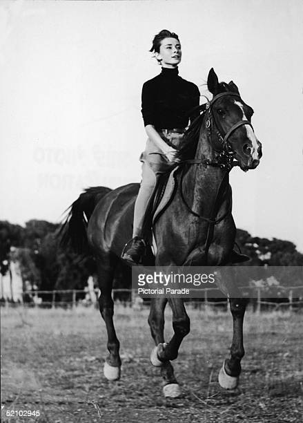 Portrait of Belgian-born American actress Audrey Hepburn as she rides a horse and wears chaps, Italy, 1955.